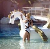 Woman relaxing in luxury swimming pool resort hotel on big inflatable unicorn floating pegasus float. Young fashion woman relaxing in luxury swimming pool resort Stock Photos