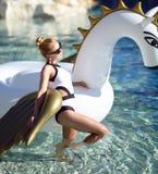 Woman relaxing in luxury swimming pool resort hotel with huge bi. Young pretty fashion woman relaxing in luxury swimming pool resort hotel with huge big unicorn Stock Photos