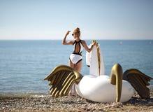 Woman relaxing in luxury swimming pool resort hotel with huge bi. Young pretty fashion woman relaxing in luxury swimming pool resort hotel with huge big unicorn Royalty Free Stock Photo