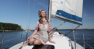 Woman relaxing on a luxury yacht. The wind blows curly hair. 4K footage stock video