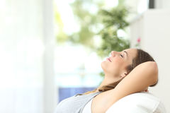 Woman relaxing lying on a couch at home Stock Photos