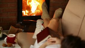 Woman relaxing, lying by the fireplace, focus on flames stock footage