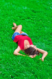 Woman relaxing lying on the grass. Young beautiful slim woman relaxing lying on the grass Stock Photo
