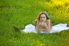 Woman relaxing lying on green grass Stock Photos