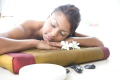 Woman relaxing on massage bed Stock Photos