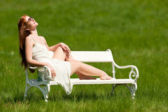 Woman relaxing in meadow in summer sun Stock Photos
