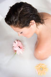 Woman relaxing in milk bath with flowers Stock Images