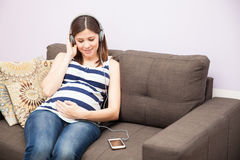 Woman relaxing with music during pregnancy. Pretty young pregnant woman listening to some calming music with a smartphone and headphones at home Royalty Free Stock Photos