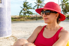 Woman Relaxing near the beach. Woman wearing a red hat and Sunglasses relaxing near the beach Royalty Free Stock Photo