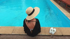 Woman relaxing near blue pool stock footage