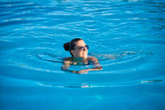 Woman relaxing near blue swimming pool Stock Photos
