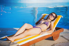 Woman relaxing near blue swimming pool Stock Photo