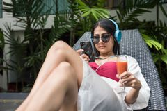 Woman relaxing near swimming pool. Portrait of sexy Asian beautiful woman in red swimsuit play smartphone, listen with earbuds to streaming music, drink tomato Stock Photography