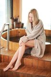 Woman relaxing near wooden barrel bath with glass in spa and sauna concept. Attractive blonde caucasian woman in bathrobe relaxing near wooden barrel bath in spa royalty free stock photos