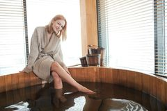 Woman relaxing near wooden barrel bath with glass of wine in hand, celebration in spa and sauna concept. Long -legged blonde young female tourist enjoying royalty free stock photos