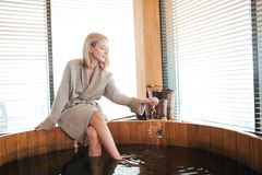Woman relaxing near wooden barrel bath with glass of wine in hand, celebration in spa and sauna concept. Long -legged blonde young female tourist enjoying stock image