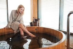 Woman relaxing near wooden barrel bath with glass of wine in hand, celebration in spa and sauna concept. Young beautiful blond woman sitting on the edge of stock photos