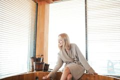 Woman relaxing near wooden barrel bath with glass of wine in hand, celebration in spa and sauna concept. Young beautiful blond woman sitting on the edge of royalty free stock photo