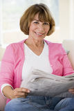 Woman relaxing with newspaper in living room Stock Image