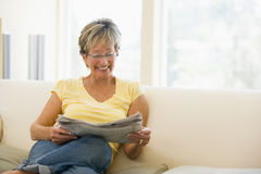 Woman relaxing with newspaper in living room Royalty Free Stock Images