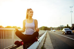Woman relaxing next to a busy road, challenge concept Stock Photos