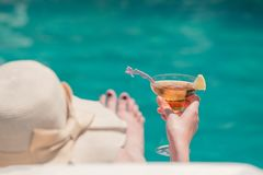Woman relaxing next to the swimming pool and holding cocktail stock photo
