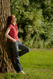 A woman relaxing next to a tree Royalty Free Stock Photography