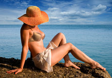 Woman relaxing by ocean. Middle aged woman wearing bikini and wide brimmed hat relaxing by ocean, cloudscape in background Stock Images