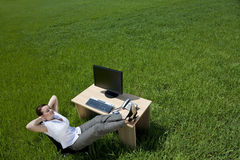 Woman Relaxing At An Office Desk In A Green Field stock photo