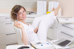 Woman relaxing in office. Holding eyeglasses in her hand Royalty Free Stock Photos
