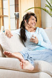 Woman Relaxing On Sofa Royalty Free Stock Photography