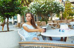 Woman relaxing in the outdoor cafe - drinking coffee and reading Stock Images