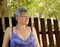Woman relaxing in an outdoor garden. Woman in a sun dress sitting on a bench relaxing in an outdoor garden royalty free stock photos