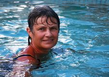 Woman relaxing in an outdoor pool. Woman portrait relaxing in an outdoor pool royalty free stock images