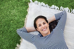 Woman relaxing outdoor. Portrait of latin woman relaxing on blanket at park. Top view of happy mature woman lying on white blanket on grass. Hispanic woman lying Royalty Free Stock Photography