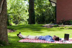 Woman relaxing outside after work. Woman relaxing after work on a blanket in her backyard Stock Photos
