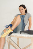 Woman relaxing with a paint roller in her hand Royalty Free Stock Image