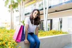 Woman Relaxing By Paper Bags After Shopping Outside Mall. Portrait of happy woman relaxing by paper bags after shopping outside mall stock photos
