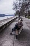 Woman relaxing on park bench. Stock Photos