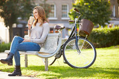 Woman Relaxing On Park Bench With Takeaway Coffee Royalty Free Stock Photos