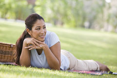 Woman relaxing in park with picnic Stock Images