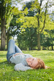 Woman Relaxing in a Park. Portrait of a woman relaxing on green grass in an empty city park Royalty Free Stock Photos