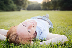 Woman Relaxing in a Park in Summer. A smiling young woman lies on her back on green grass at an outdoor park on a summer afternoon and looks at the camera Royalty Free Stock Photography