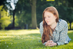 Woman Relaxing in a Park. Young casual woman with long red hair relaxes on green grass in a park Stock Photo
