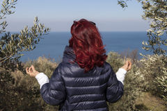 Woman relaxing, performing joga on sea coast. Pretty middle aged woman with red hair meditating, performing joga in beautiful organic olive grove above the sea Royalty Free Stock Images