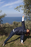 Woman relaxing, performing joga on sea coast Royalty Free Stock Image