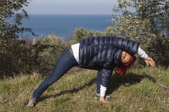 Woman relaxing, performing joga on sea coast. Pretty middle aged woman with red hair meditating, performing joga in beautiful organic olive grove above the sea Stock Images