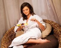 Woman relaxing with plate of fruits Stock Photos