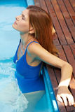 Woman relaxing in pool Stock Photo