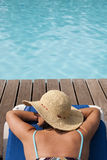 Woman relaxing at the pool Stock Images
